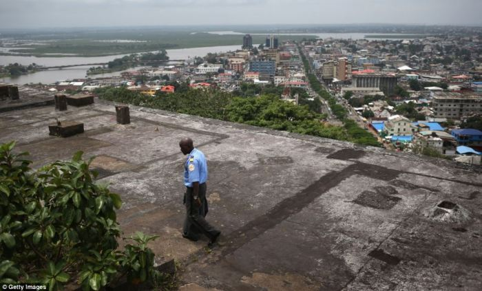 A security guard walks atop the roof of an abandoned hotel in Monrovia