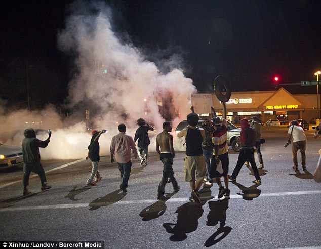 Chaos: Smoke from a tire burnout rises over protestors on West Florissant Avenue during a tense demonstration