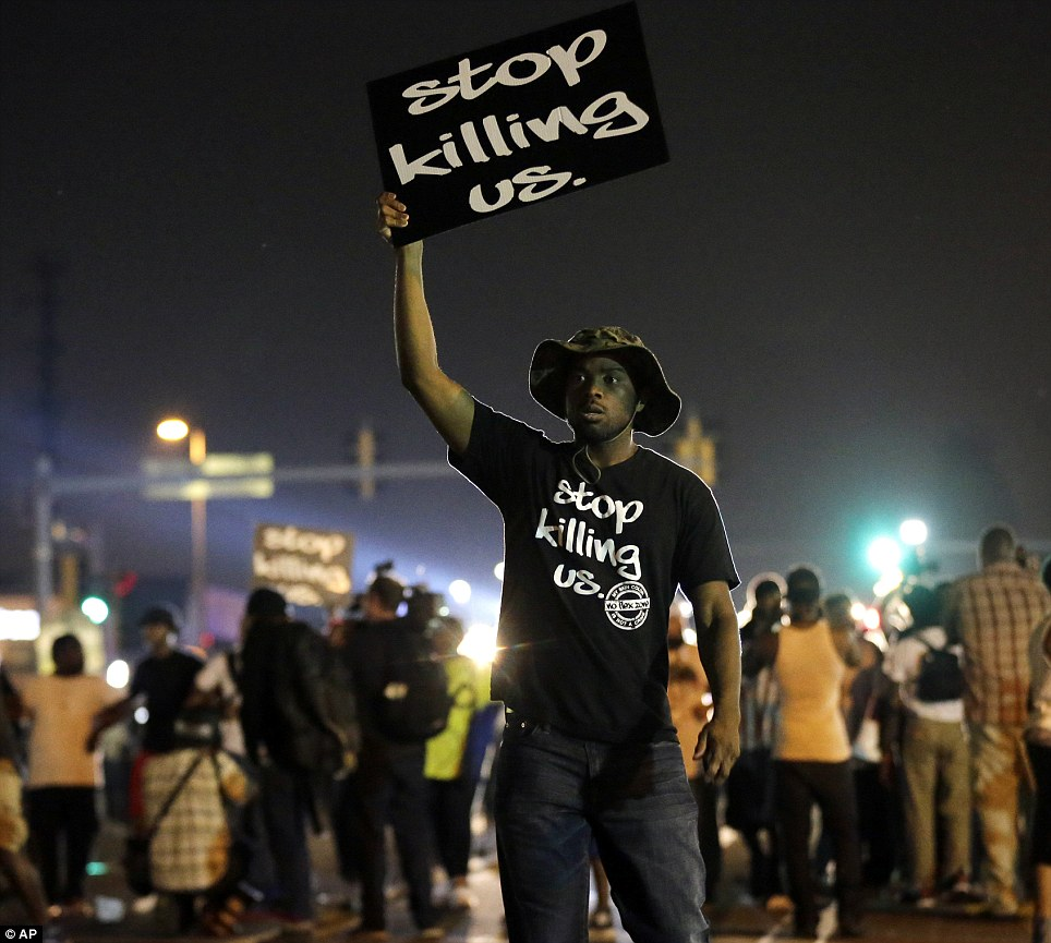 The scene was relatively peaceful until midnight when tense standoffs lead to police throwing teargas and stun grenades amid high racial tensions in Ferguson