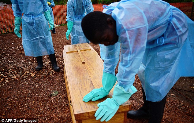 Sierra Leonese government burial team members wearing protective clothing stand next to the coffin of Dr Modupeh Cole, Sierra Leone's second senior physician to die of Ebola in Kailahun