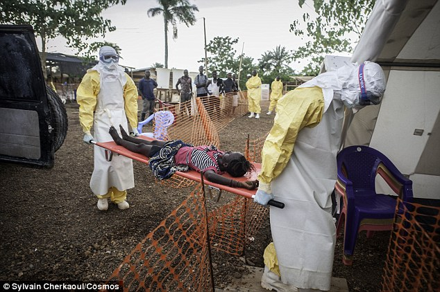 Two medical staff are bringing a weak patient who has been in contact with people infected with Ebola to the admission