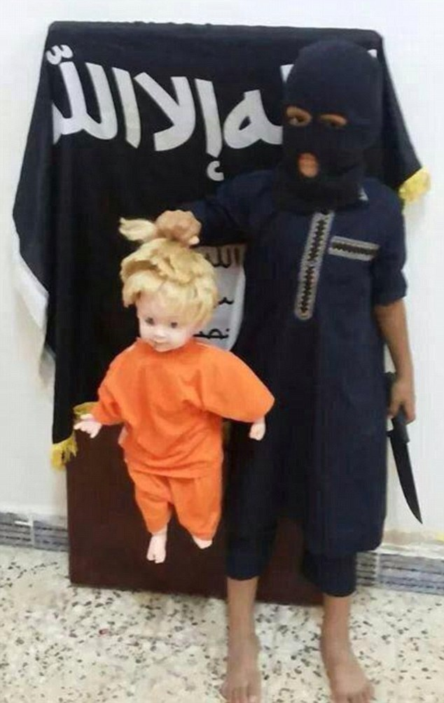 Chilling: Barefoot and wearing a black balaclava, a young child appears to re-enact the brutal murder of the U.S. journalist James Foley by beheading a doll in an orange jumpsuit. The images were circulated on Twitter