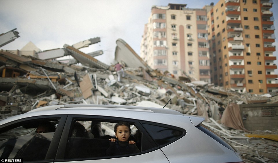 Morning after: A young Palestinian boy looks out of a car window as it drives past the rubble of the residential tower