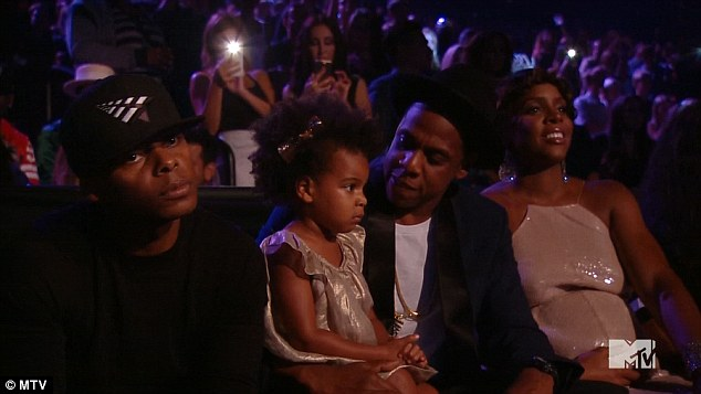 Keeping close: Beyonce's two-year-old daughter remained on her father's knee during her 20 minute medley of her latest album, while pregnant Kelly, 33, was perched next to him