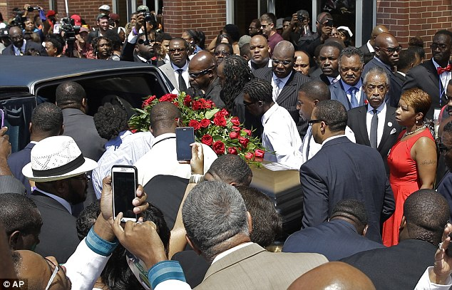 People gather outside of Friendly Temple Missionary Baptist Church as Michael Brown's mother Lesley McSpadden, right, Rev. Al Sharpton, and Rev. Jesse Jackson follow the casket during the funeral for Michael Brown