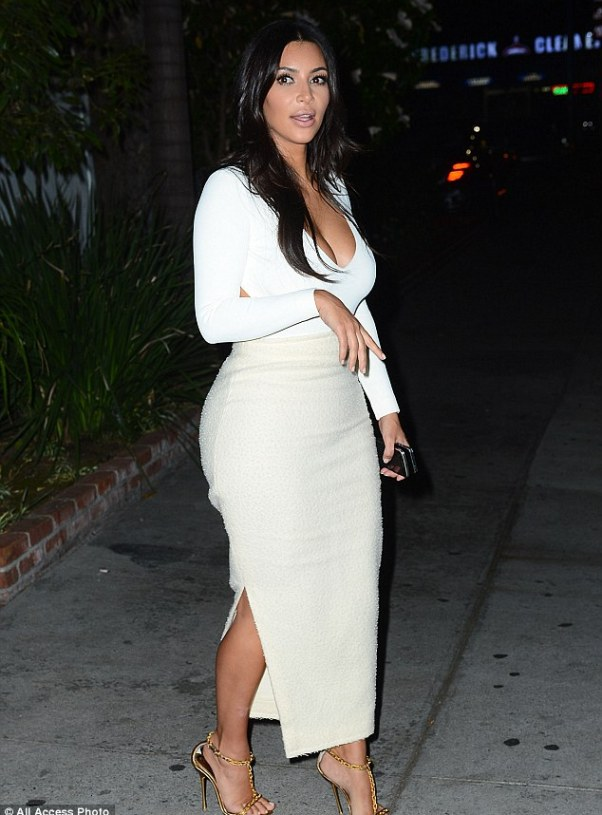 Va va voom: Kim showed off her bombshell curves as she stood on the pavement clutching two cellphones