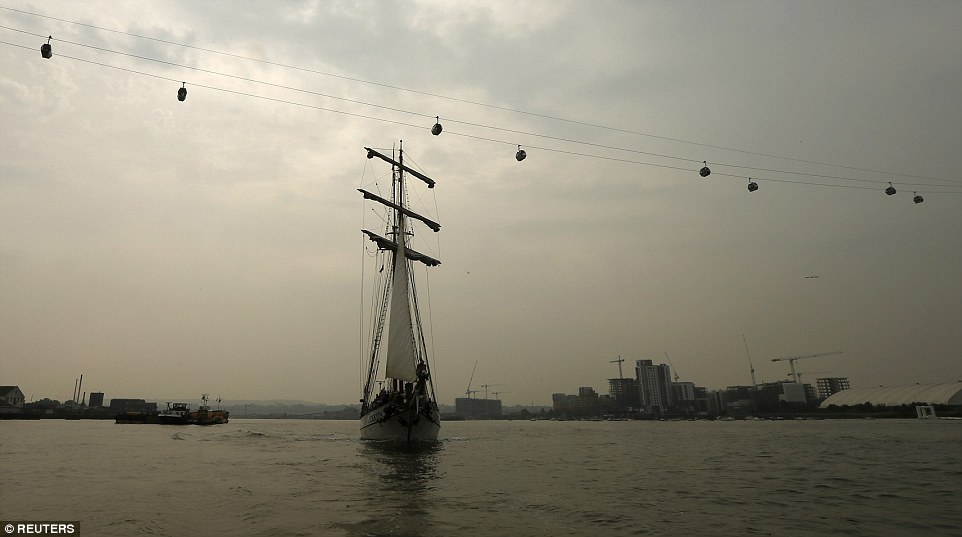 The Tall Ship JR Tolkien is pictured sailing under the Thames cable car early this morning. Ships have come from all over the world to take part in the festival