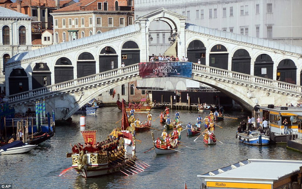 A pequena frota de gôndolas navegar sob a Ponte Rialto sobre o Grande Canal, como parte da Regata Storica anual - um concurso anual que recria a tradição de desfilar barcaças e barcos, uma vez que beneficiam os líderes da antiga República de Veneza