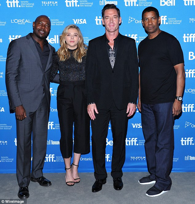 Holding her own: The petite blonde posed with The Equalizer director Antoine Fuqua and her big gun co-stars Marton Csokas and Denzel Washington