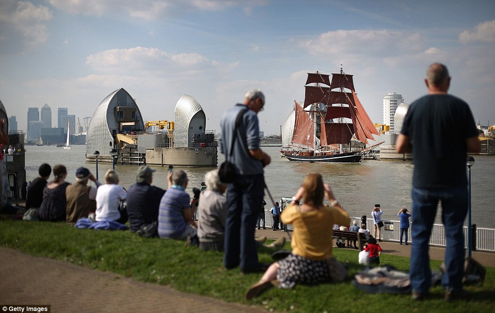 A crowd gather on the grass banks alongside the Thames to watch the procession. Some use their phones to take pictures of the historic vessels