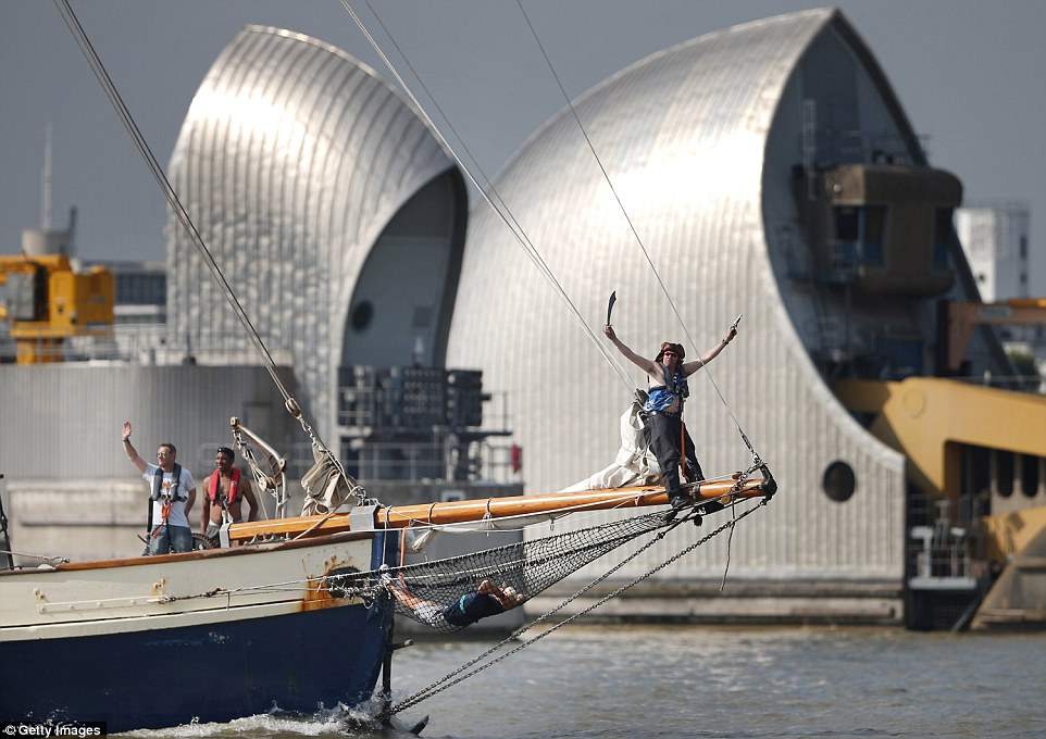 A crew member, dressed as a pirate, balances on the bow of the ship as it sails through the Thames Barrier. Another two behind him wave to spectators
