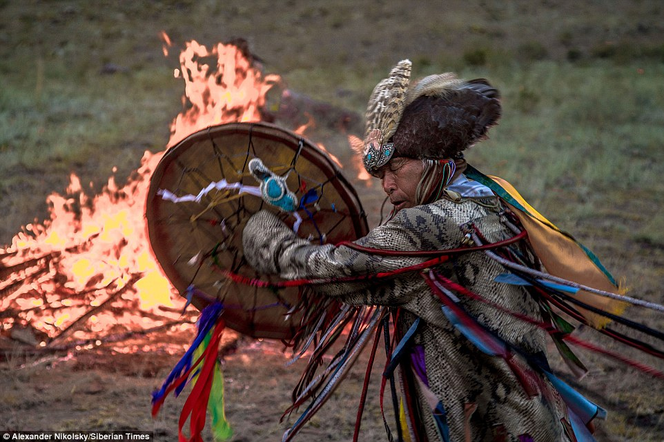 A shaman performs a ritual next to a fire in a remote part of the Siberian mountains.  It's part of the festival 'Call of 13 Shamans' held near the village of Khorum-Dag in Tyva Republic, the geographic centre of the Asian continent