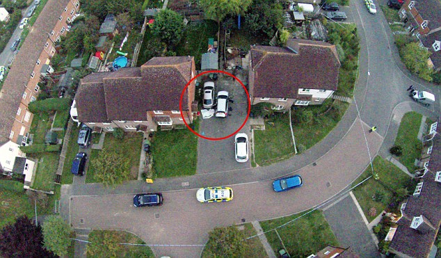 This aerial shot shows the gunman's car, circled right with open doors, and his body covered by a blanket
