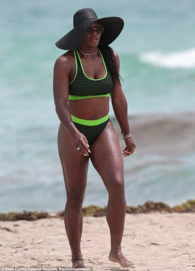 Champ: US Open Winner Serena Williams relaxes on Miami Beach in Florida in a black and lime green bikini