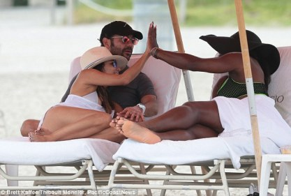 Famous friends: Serena and Eva high-fived as they reclined on sun loungers at the beach