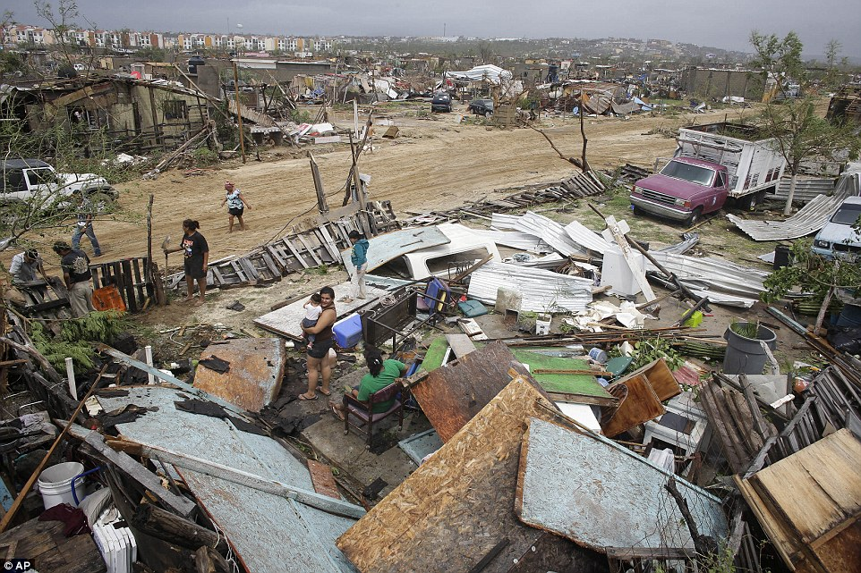 Devastation:  Residents salvage the useful remains from houses destroyed by Hurricane Odile in Los Cabos, Mexico, today. Hundreds for impoverished housed were destroyed
