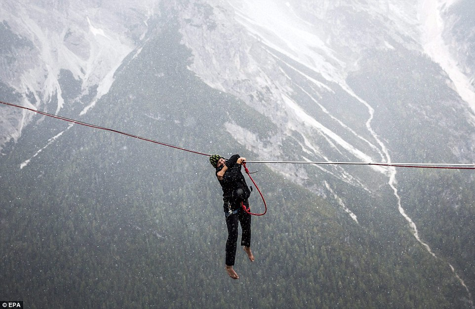 Now get back up there: Losing your footing results in the inevitable, but a small safety rope stops this high wire enthusiast from plummeting to his death