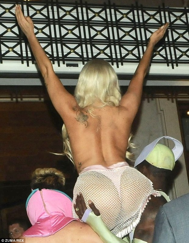 Looking booty-ful! Carried by two Lycra-clad hunks as she made her way through the crowds, the 28-year-old pop princess was clad merely in a skimpy shell bra and a racy thong while stepping off her private plane