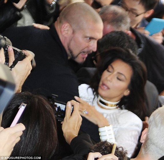 Dramatic scenes: Kim Kardashian was almost pulled to the ground by red carpet gate crasher Vitalii Sediuk at Paris Fashion Week on Thursday