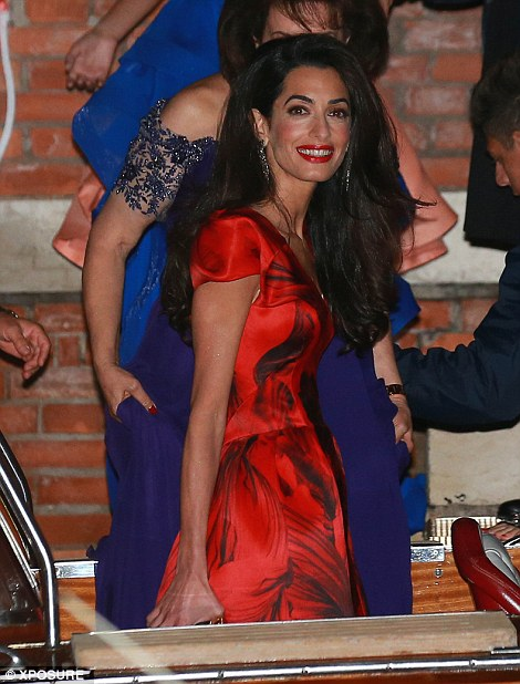 Glam to the max: Amal wore her dark locks in a voluminous style and added a red lip colour to complete her fiery outfit