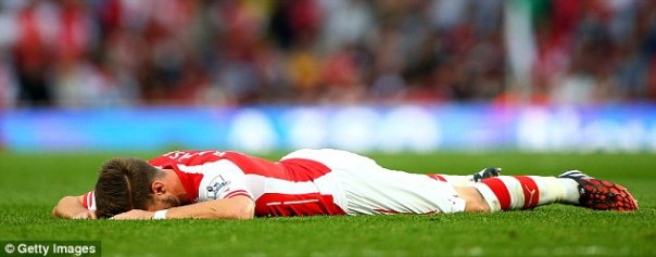 Aaron Ramsey lies on the pitch after picking up an injury during the Premier League match on Saturday
