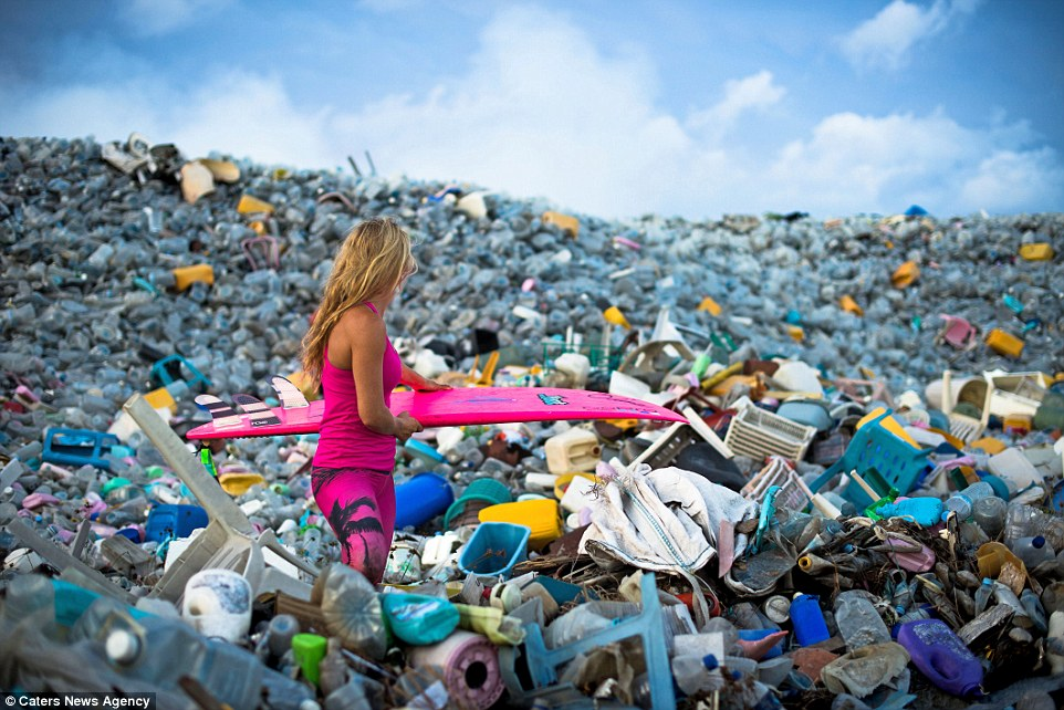 Dark side of paradise: Alison Teal pictured with her surfboard while walking through mountains of rubbish on Thilafushi in the Maldives