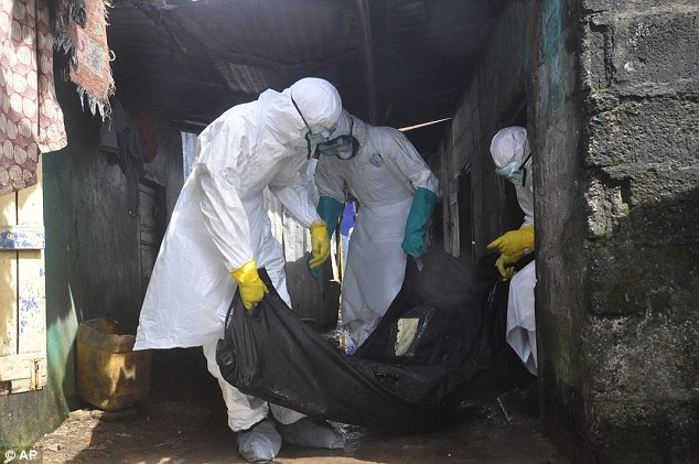 Health workers in protective gear remove the body of a woman suspected to have died from the Ebola virus, near the area of Freeport in Monrovia, Liberia on Wednesday. Mr Duncan reportedly helped carry his landlord's gravely-ill daughter to hospital before boarding a plane to the U.S.