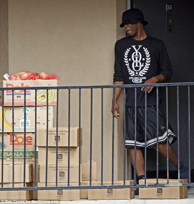 An unidentified man exits the apartment under quarantine for Ebola today to pick up food that was delivered by The Red Cross in Dallas, Texas. The young man is wearing a shirt that reads: 'YOLO, you only live once'