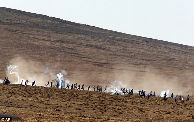 Turkish youths clash with government forces during an anti-ISIS protest close to the border with Syria - ozara gossip