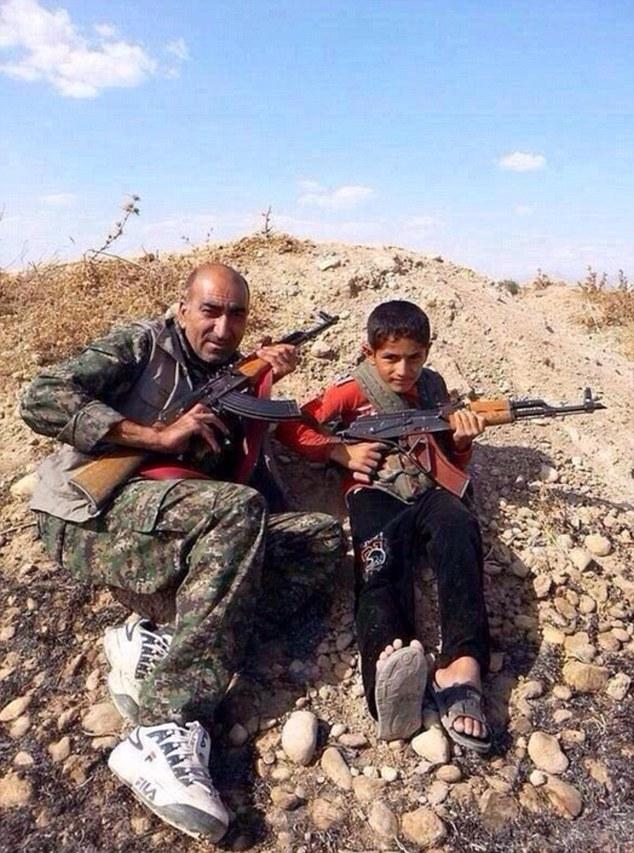 man and son, pose holding AK-47s while defending Kobani | ozara gossip
