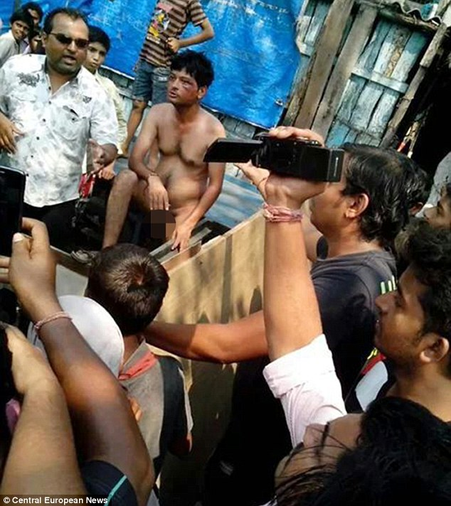 Kumar, middle, is stripped naked and awaits his fate, as locals record the punishment he is about to face