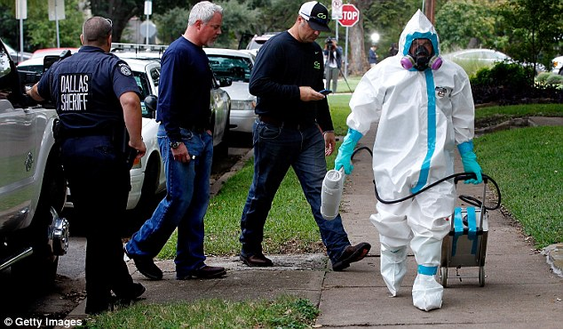 Clean up: A  man in full hazmat clothing walks in front of Pham's home after disinfecting the front porch
