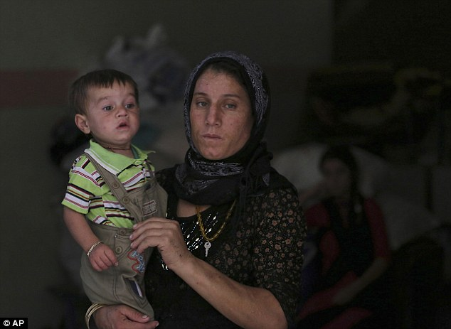 Hope: A Yazidi woman and her child are seen taking shelter at a school in Dahuk, northern Iraq