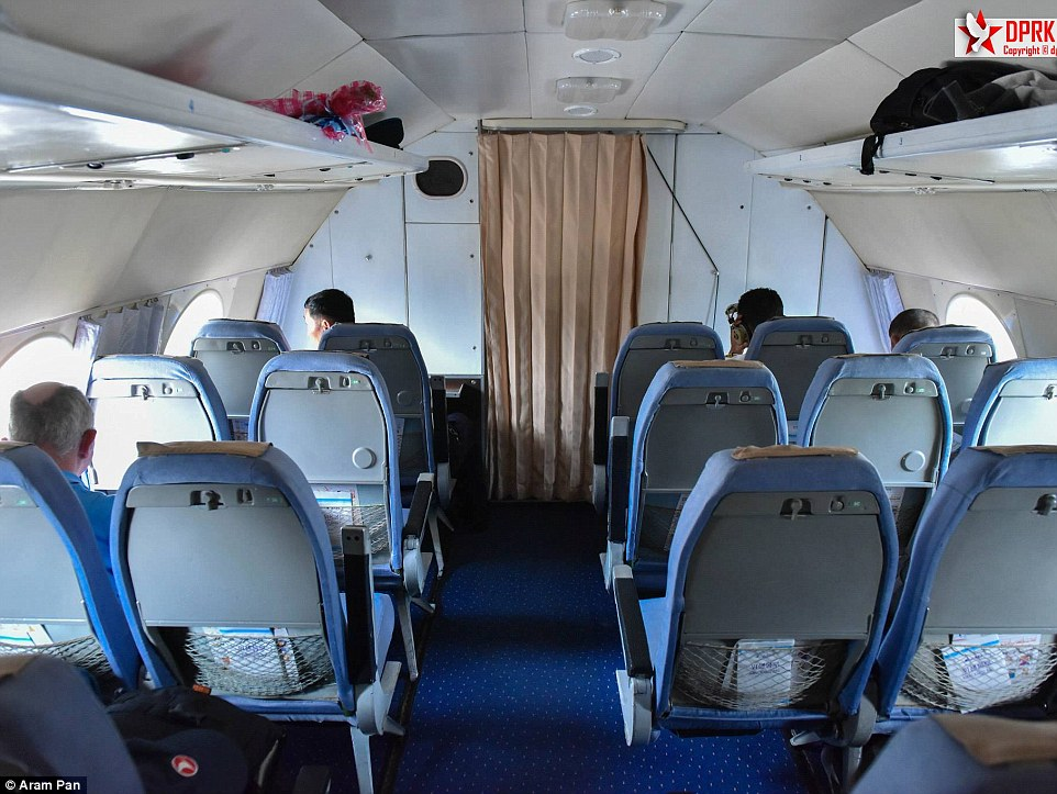 Inside the Ilyushin Il-18 there are blue chairs and blue carpet. Curtains draw across the windows and overhead luggage is stored less securely than in modern planes