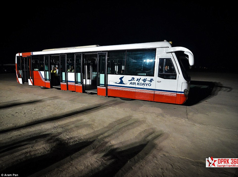 A red, white and blue Air Koryo shuttle boss transports passengers from the terminal to the planes