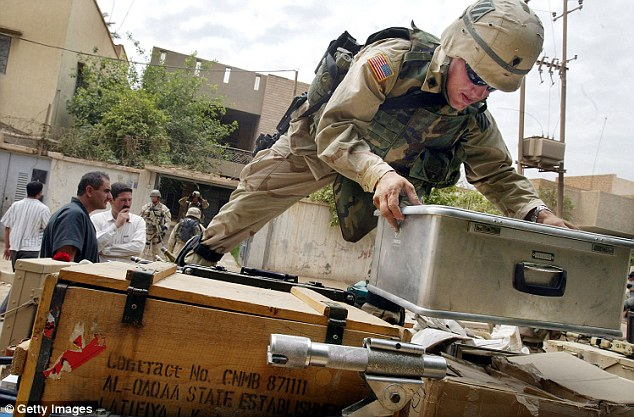A U.S. Army Third Infantry Division soldier loads materials discovered in an explosives laboratory hidden in a home April 15, 2003 in Baghdad, Iraq