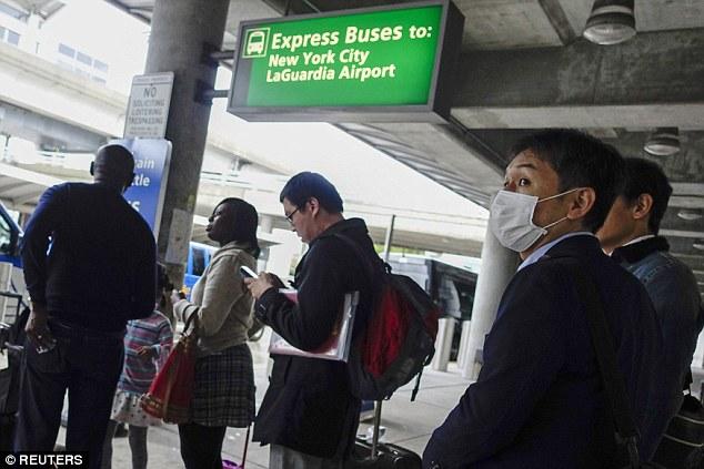 Los pasajeros fueron fotografiados uso de máscaras faciales en el aeropuerto internacional JFK en Nueva York.  Screening Ébola también está en marcha en el aeropuerto, pero los expertos en salud estadounidenses dicen que prohíbe los pasajeros procedentes de África Occidental sería una mala idea