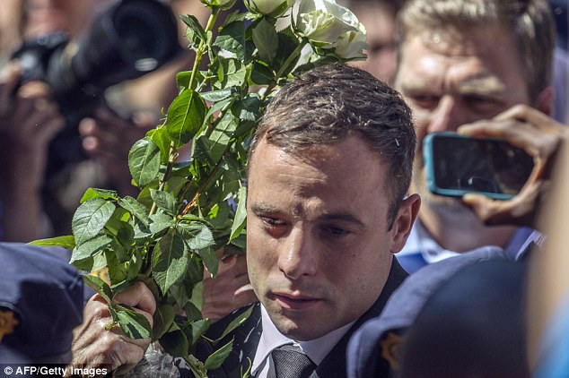 Paralympic athlete Oscar Pistorius makes his way past a bunch of roses as he enters the High Court