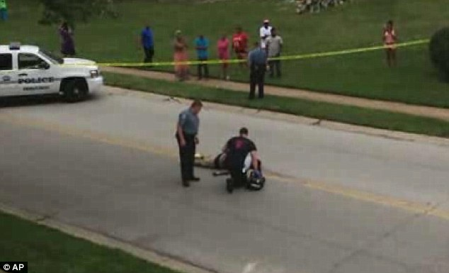 Immediate response: In this image investigators crowd round Brown's body immediately after the shooting