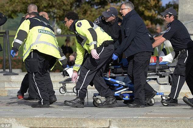Gunned down: Cirillo is raced to an ambulance after he was fatally shot in the abdomen by a gunman as he stood guard at the National War Memorial outside the Canadian Parliament Wednesday morning