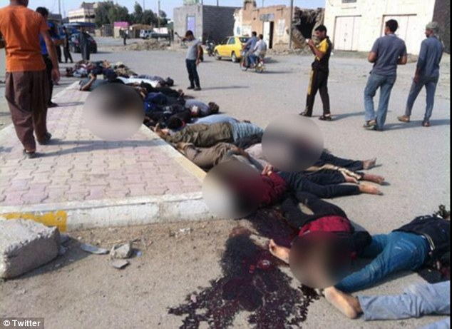 Massacre: Young men use mobile phones to take pictures of the dead bodies inside Hit this afternoon