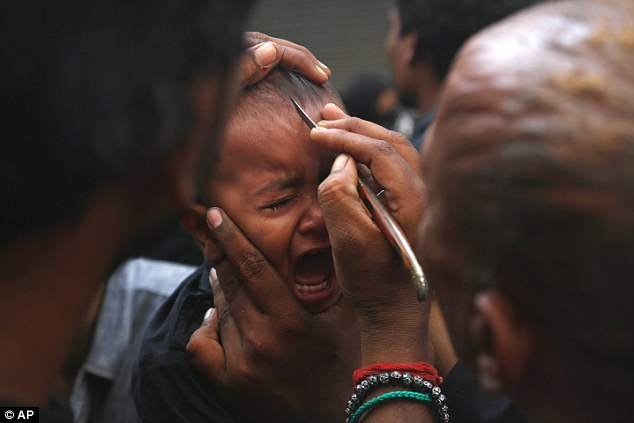 The small child cries as an adult cuts his forehead as part of the Day of Ashura, a major Shi'ite holiday
