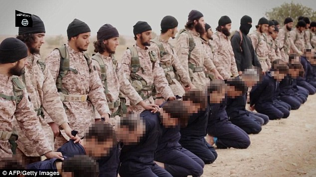 Unmasked: The 16 followers of Jihadi John prepare to behead the Syrian soldiers they have held hostage. Nasser Muthana from Cardiff isto the right of John, who is dressed in black with a balaclava