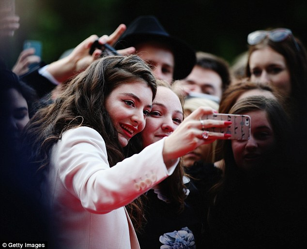 Say cheese! The Royals singer took selfies with fans as she arrived at the annual awards ceremony