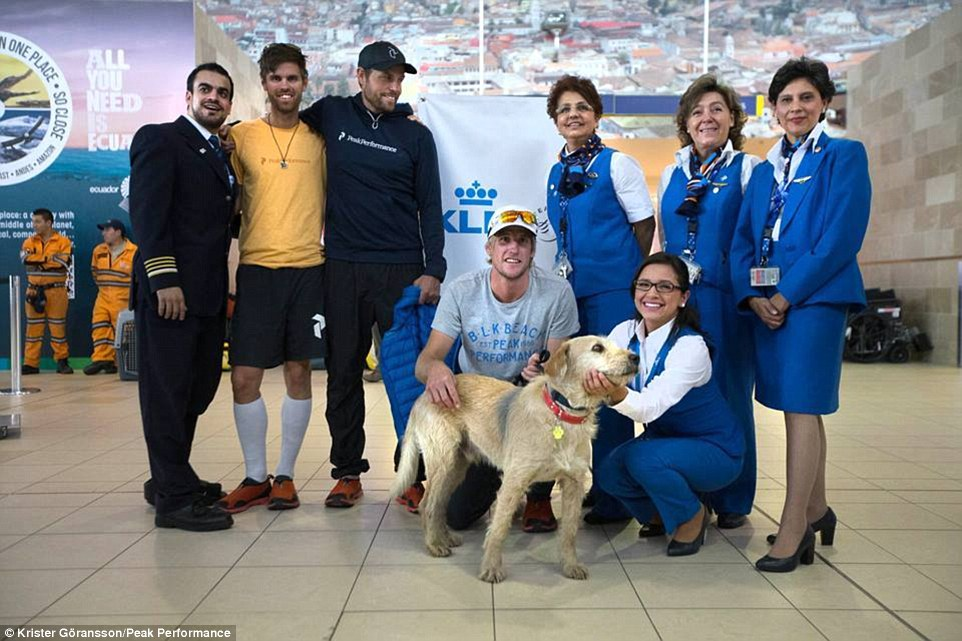 Pose: Members of the team stand alongside with flight attendants and a pilot as they prepare to take Arthur home to his new family