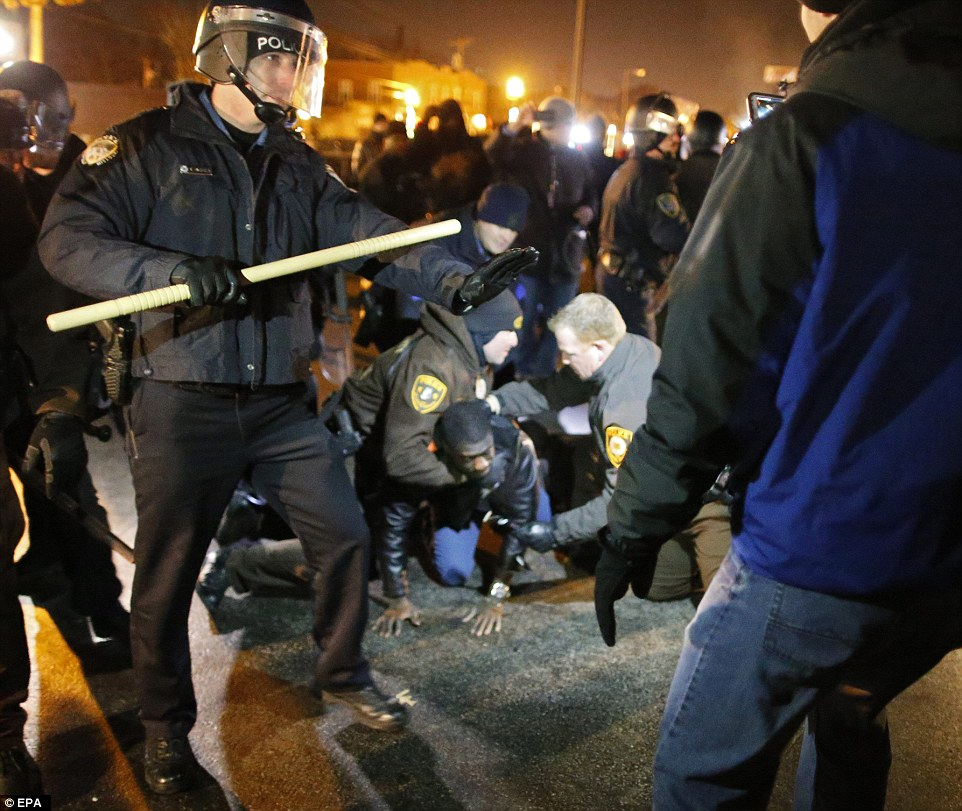 Police rush in to break up protesters outside the Ferguson Police Station