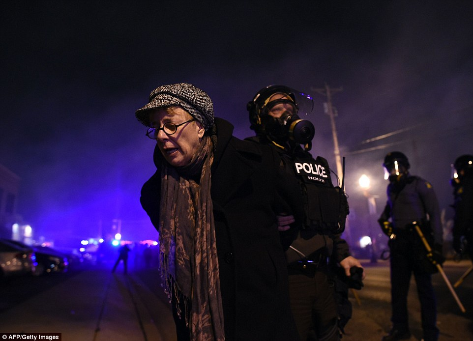 Arrested: Police detain a demonstrator amid tear gas during a demonstration to protest the death of 18-year-old Michael Brown in Ferguson, Missouri