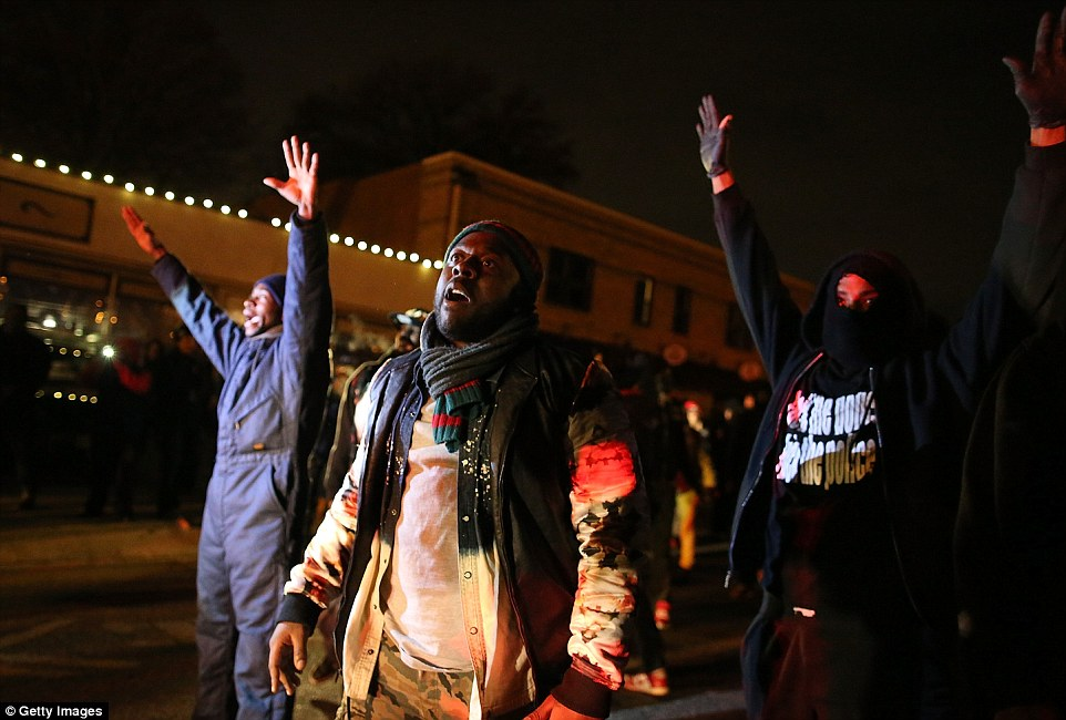 Fury: Protestors stand with their hands up during a demonstration on November 24, 2014 in Ferguson, Missouri. A St. Louis County grand jury has decided to not indict Ferguson police Officer Darren Wilson in the shooting of Michael Brown