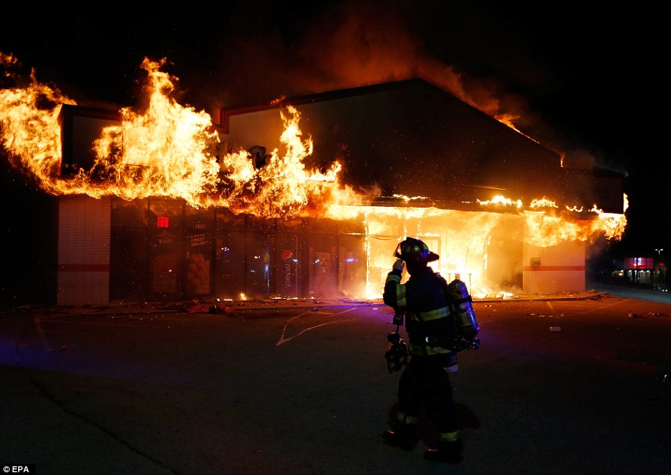 Race: A firefighter walks past the burning Little Ceasars restaurant in Ferguson on Monday. Within a few hours, several large buildings were ablaze, and frequent gunfire was heard