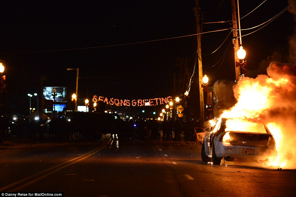 Seasons Greeting: Protestors decided to set parts of the city alight - including this vehicle - just on shot of a festive street sign